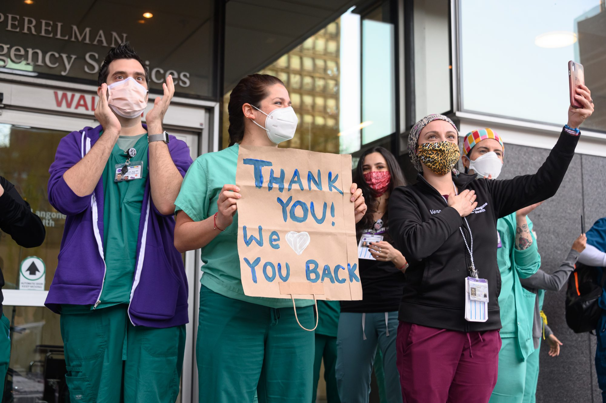 Hospital staff hold up signs to thank people for donations