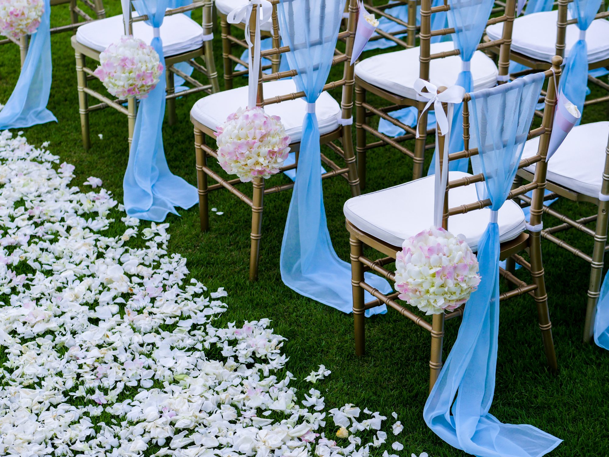 Wedding ceremony aisle chairs with blue decorations