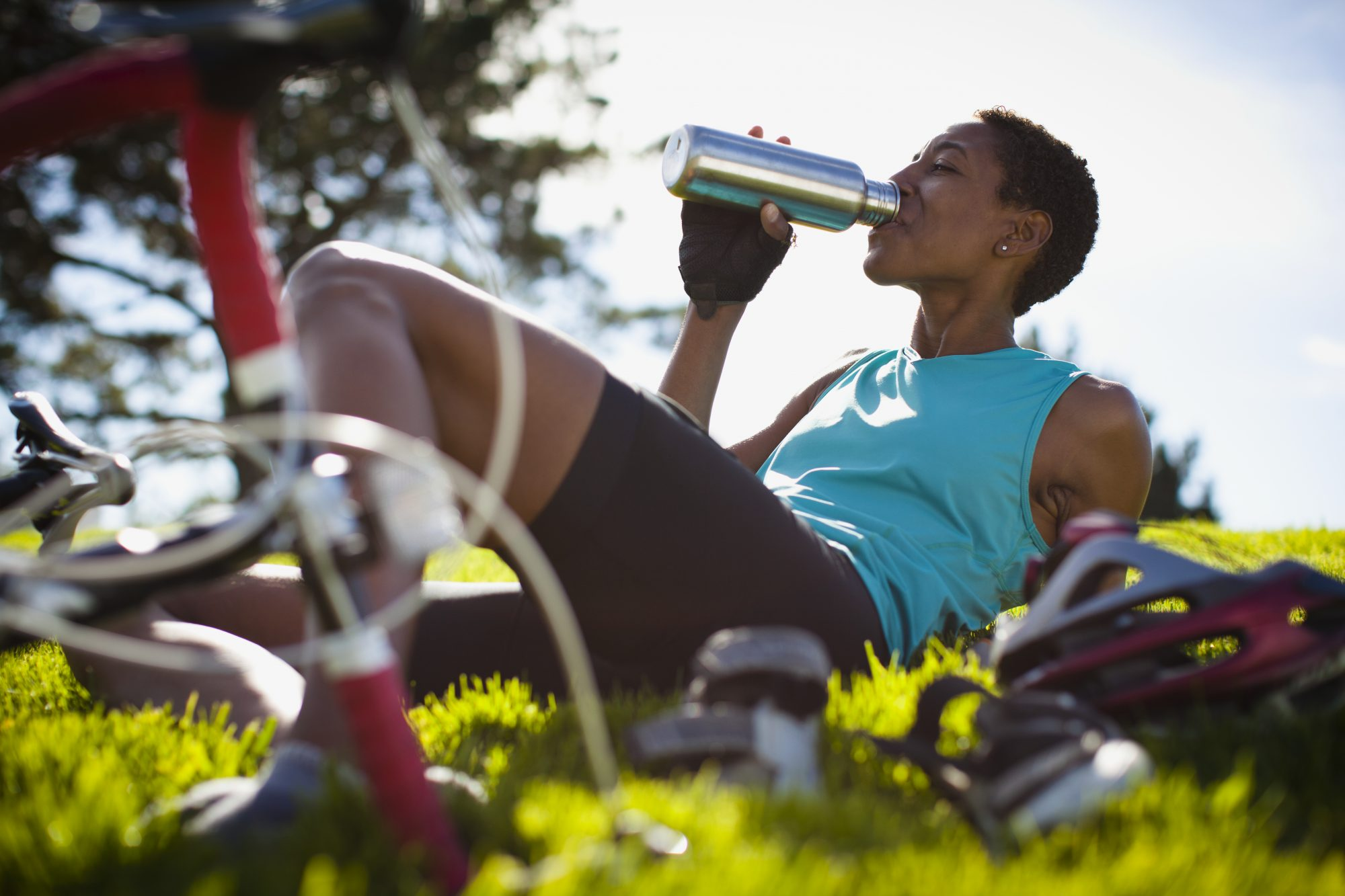 Woman drinking water and sitting in the grass after a bike ride out