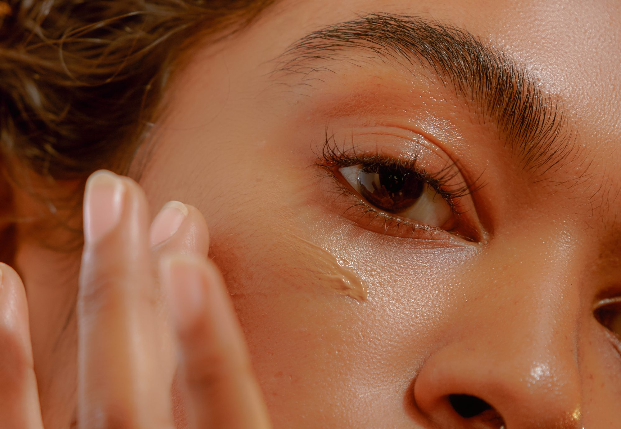 Closeup of a Young Confident Woman Applying Transfer-Proof Foundation