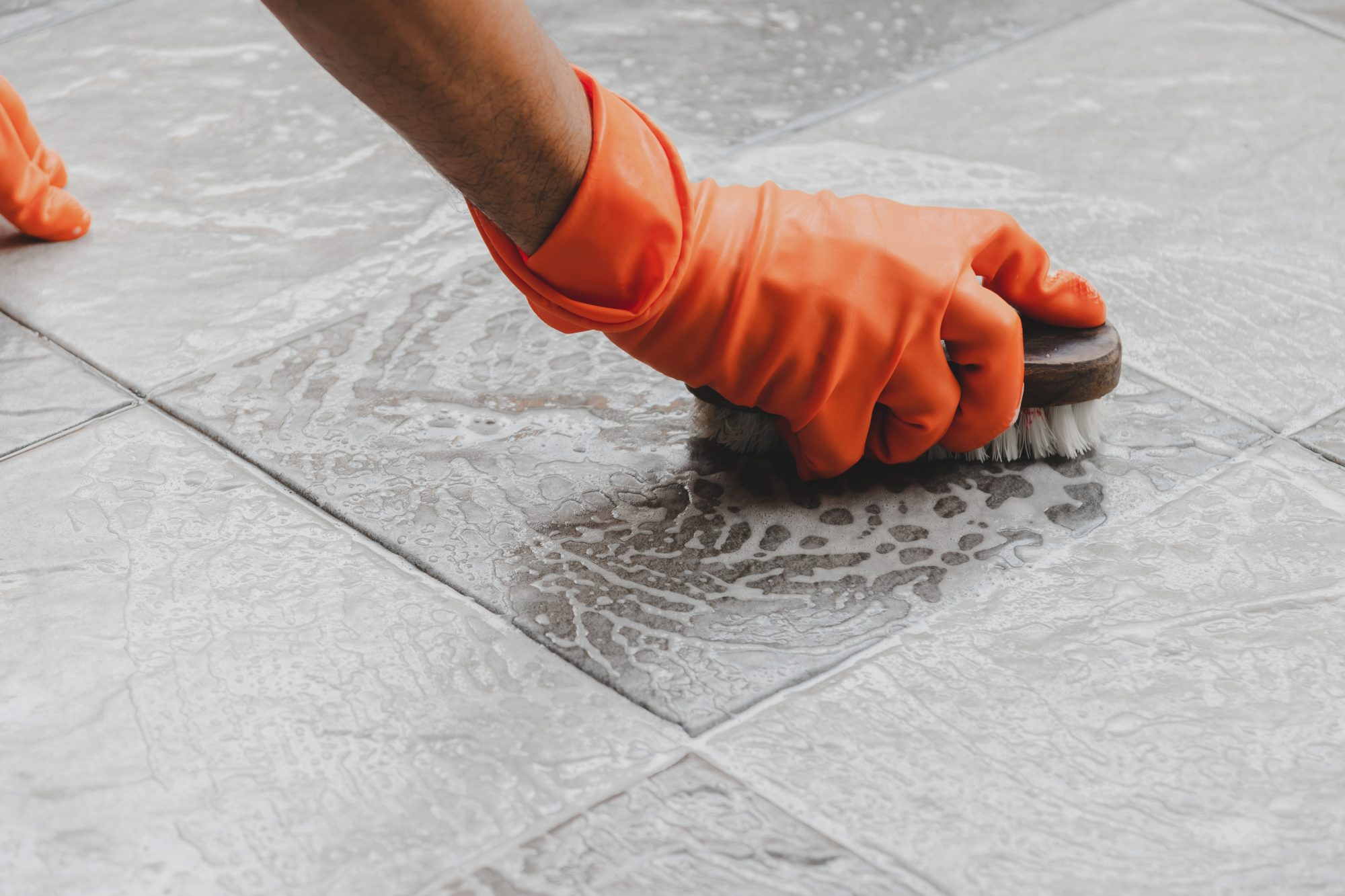 woman scrubbing floor with brush