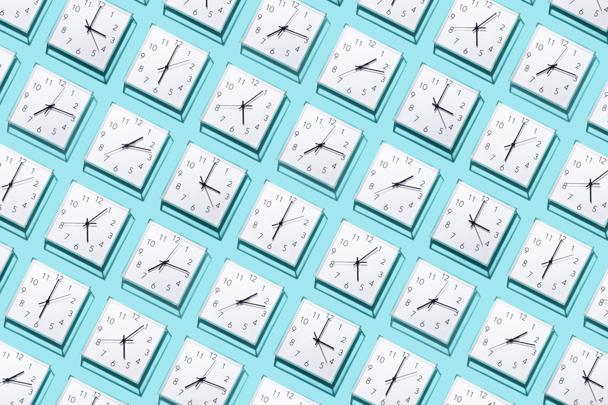 Neatly Arranged White Colored Wall Clocks Displays Different Time on Solid Blue Background
