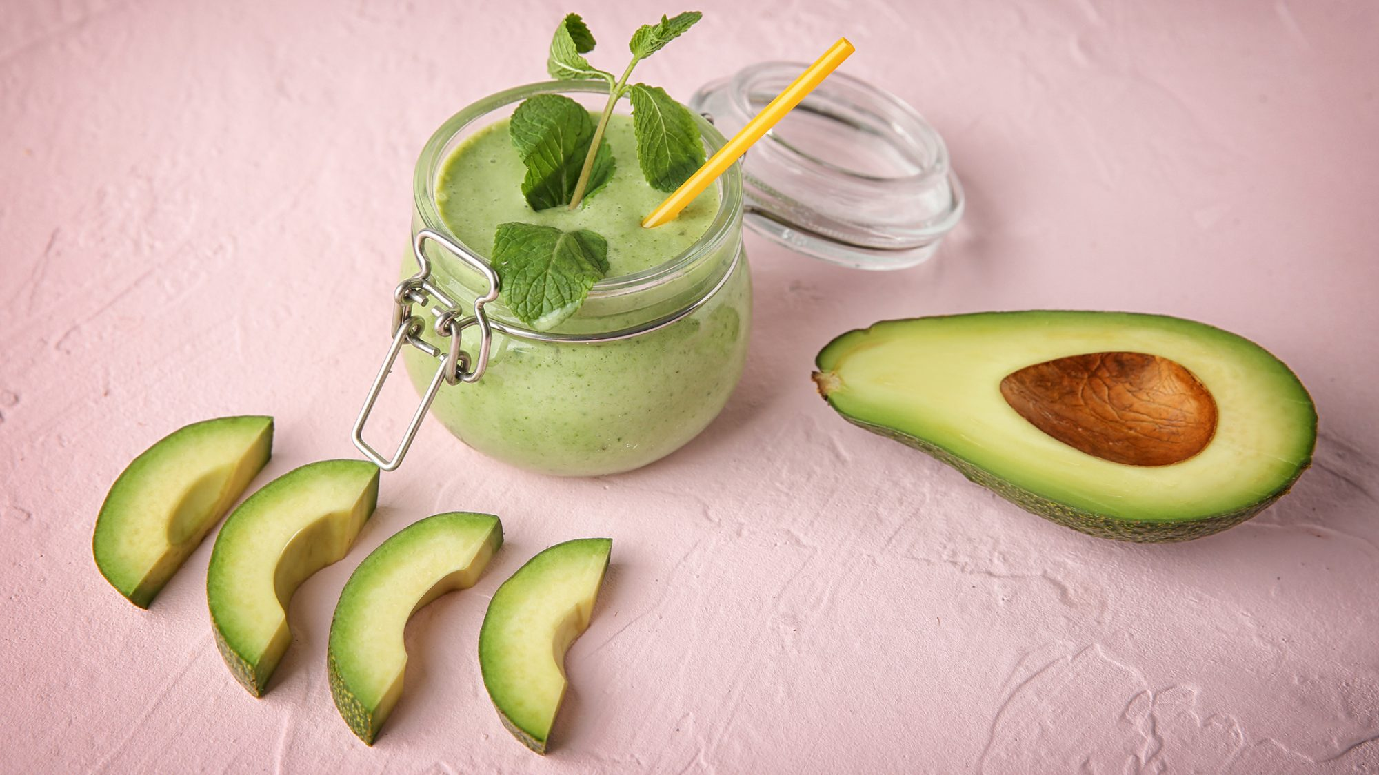 can you freeze avocado: Glass jar with tasty smoothie and sliced fresh avocado on table