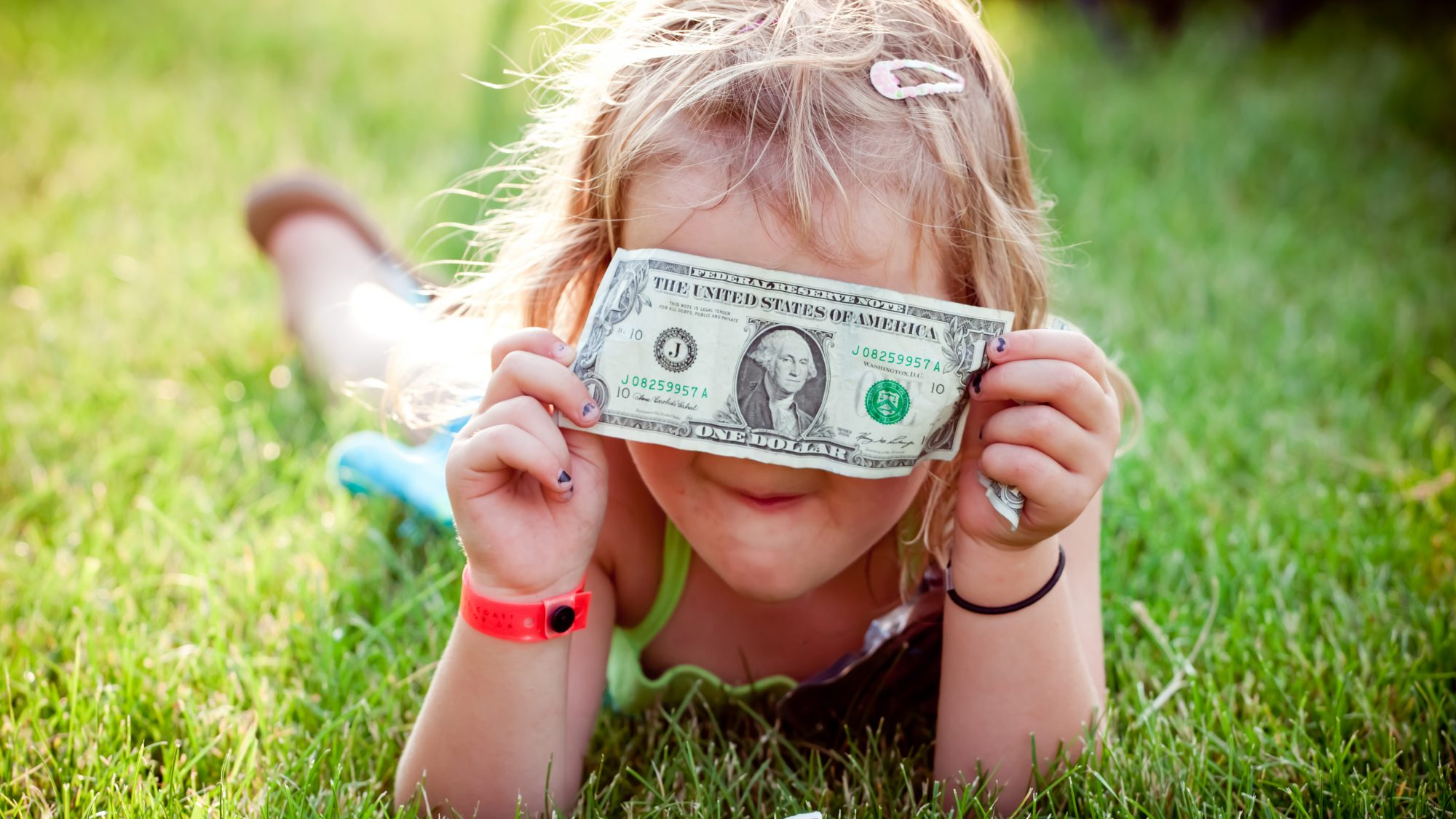 How to talk to kids about money - dos and don'ts (child with dollar)