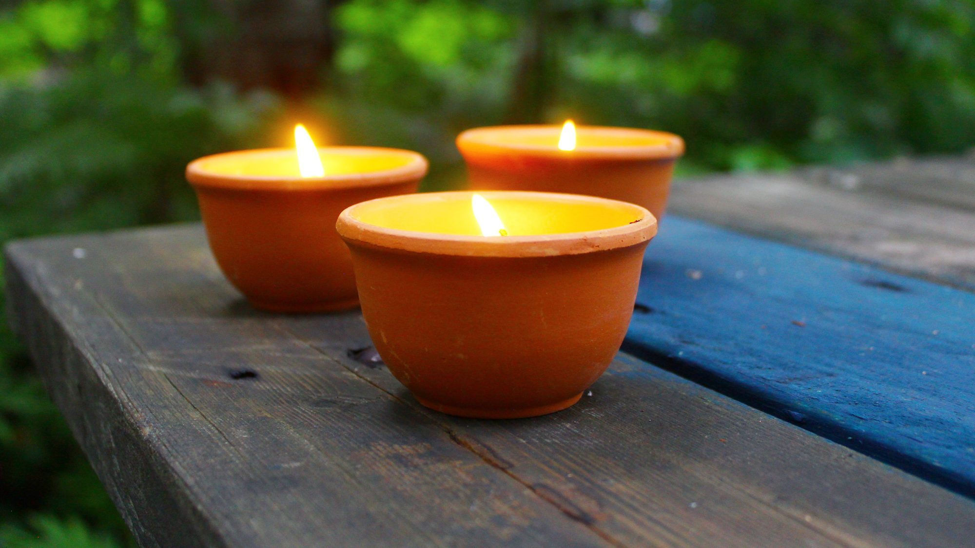Lit candles placed outside on a wood table