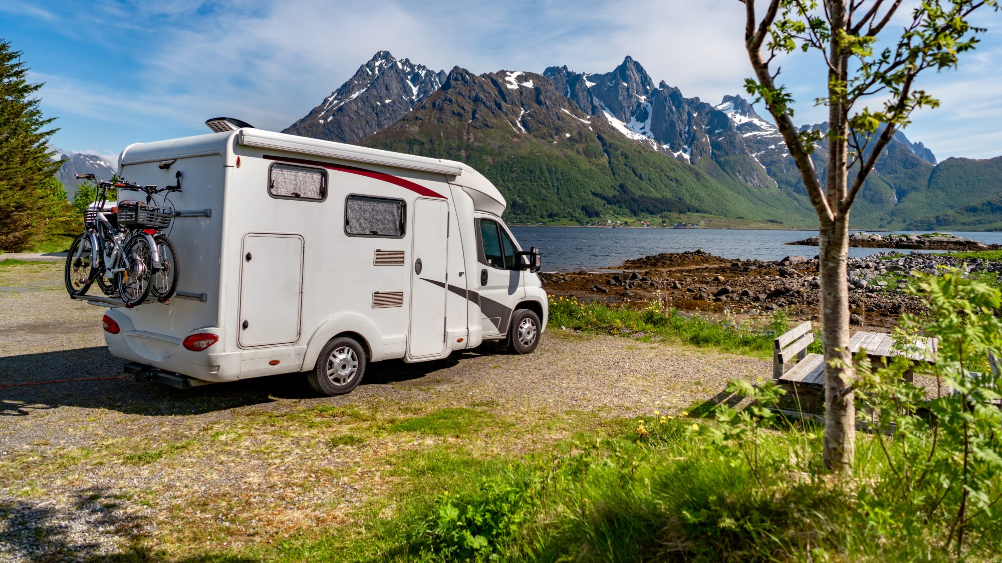 RV parked near a scenic lake and mountains