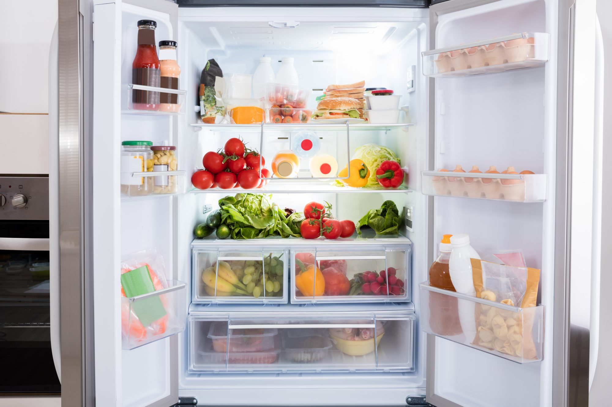 Refrigerator full of produce and groceries