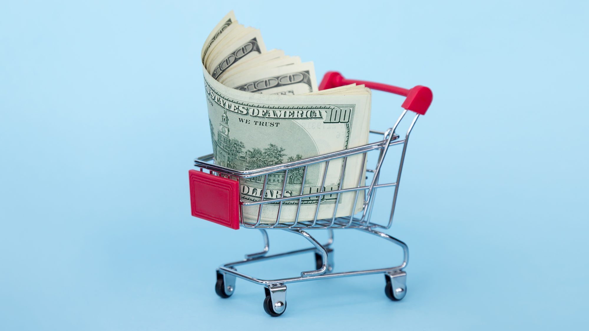 Close-Up Of Money In Shopping Cart Against Blue Background