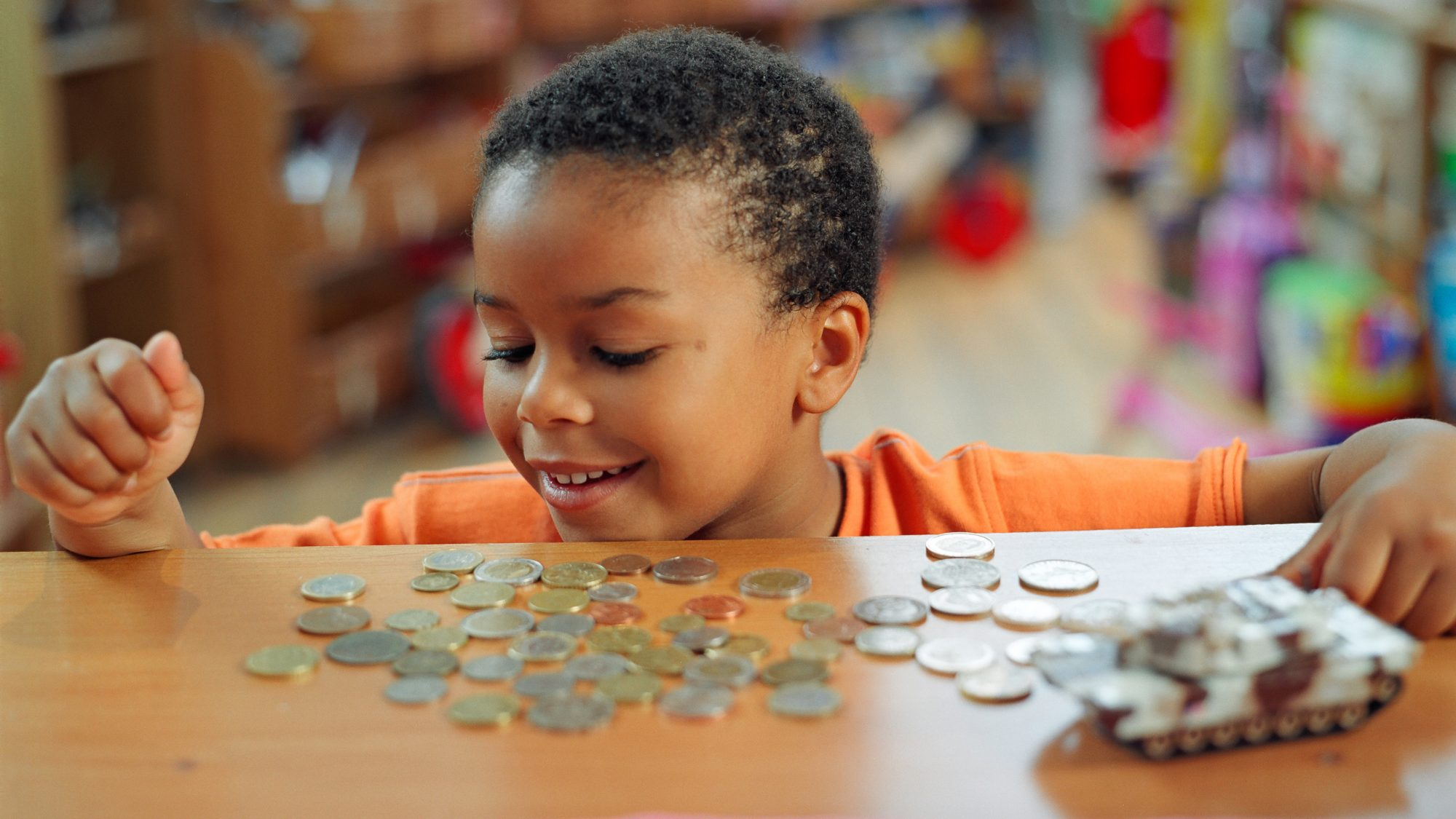 Boy (4-6) counting out change on counter in toy shop, smiling