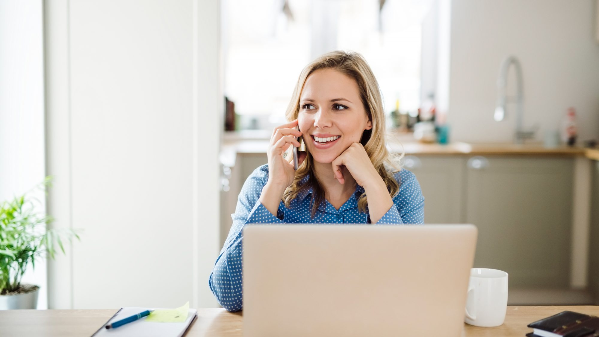 Blonde woman on the phone working at a desk on her laptop
