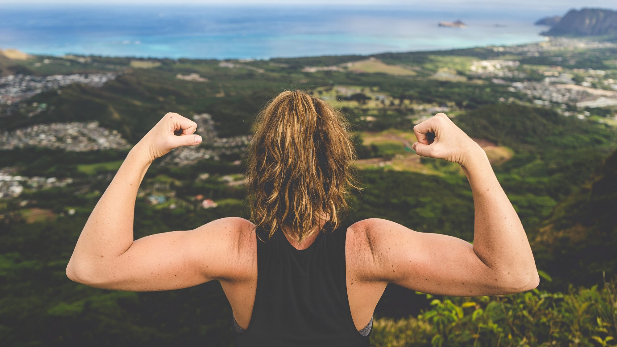 How to build resilience - strengthening resiliency muscle (woman flexing)