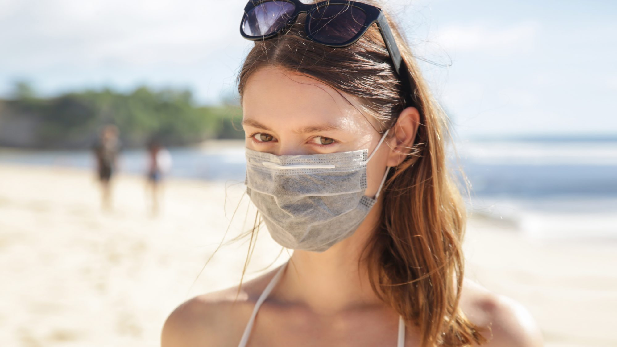 Woman wearing protective face mask on the beach. Summer vacation after Coronavirus pandemic crisis.