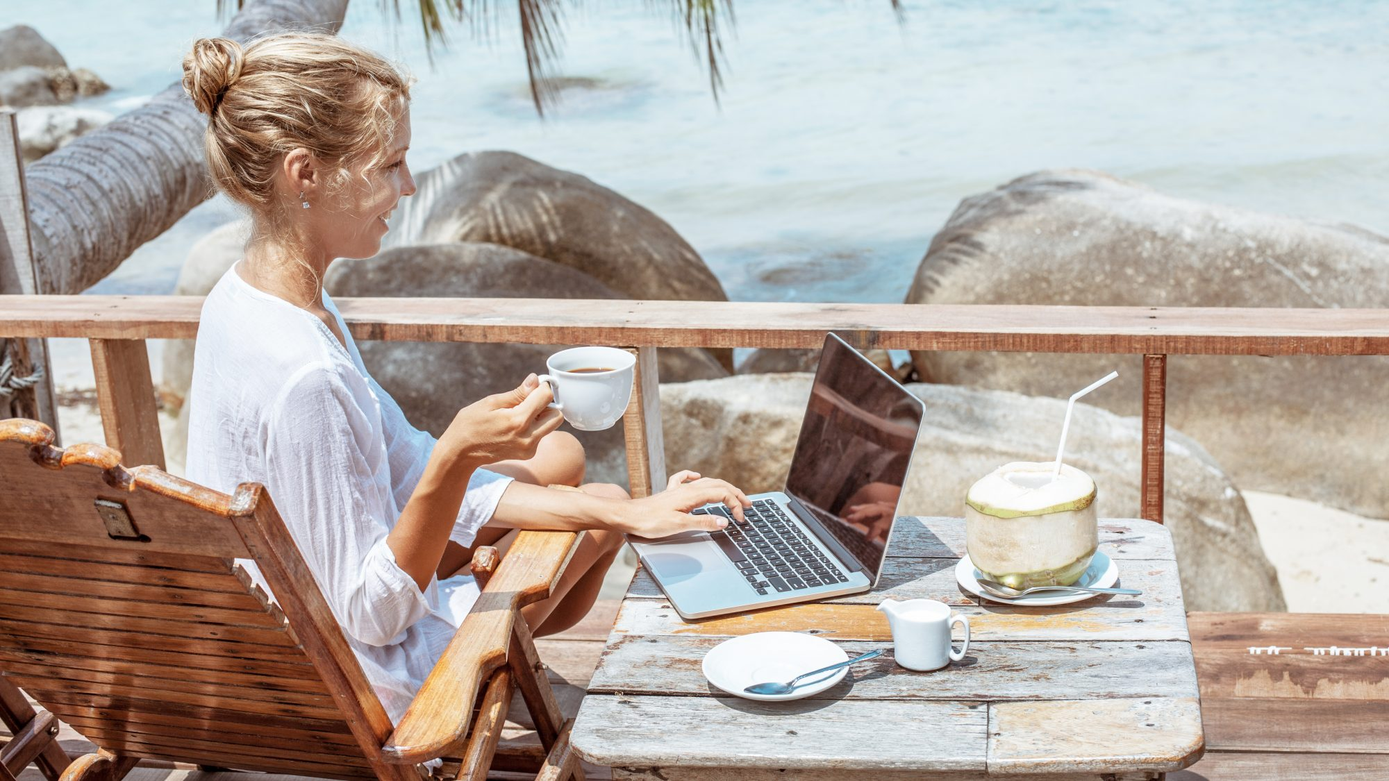 Work-cation tips - woman working by ocean
