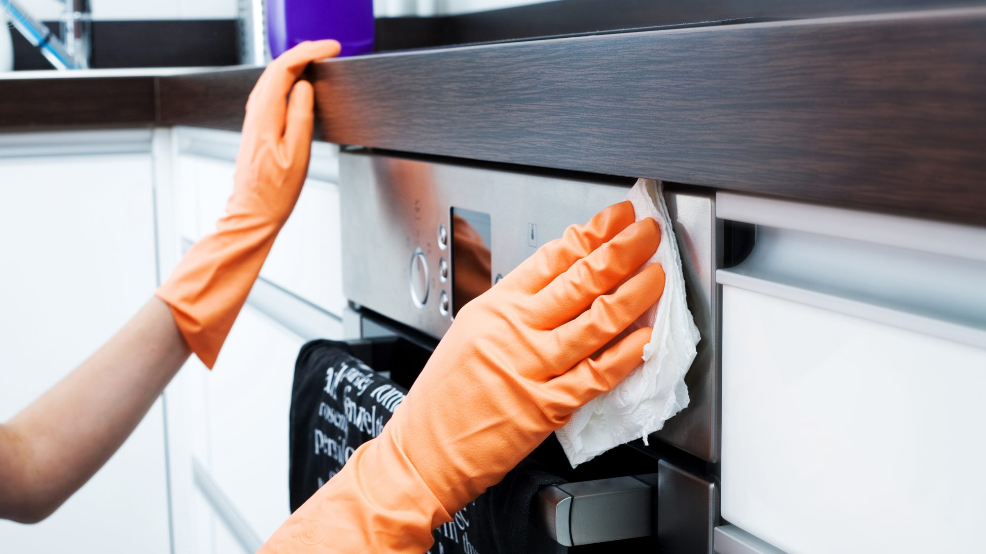 Woman Cleaning Oven in Airbnb to disinfect
