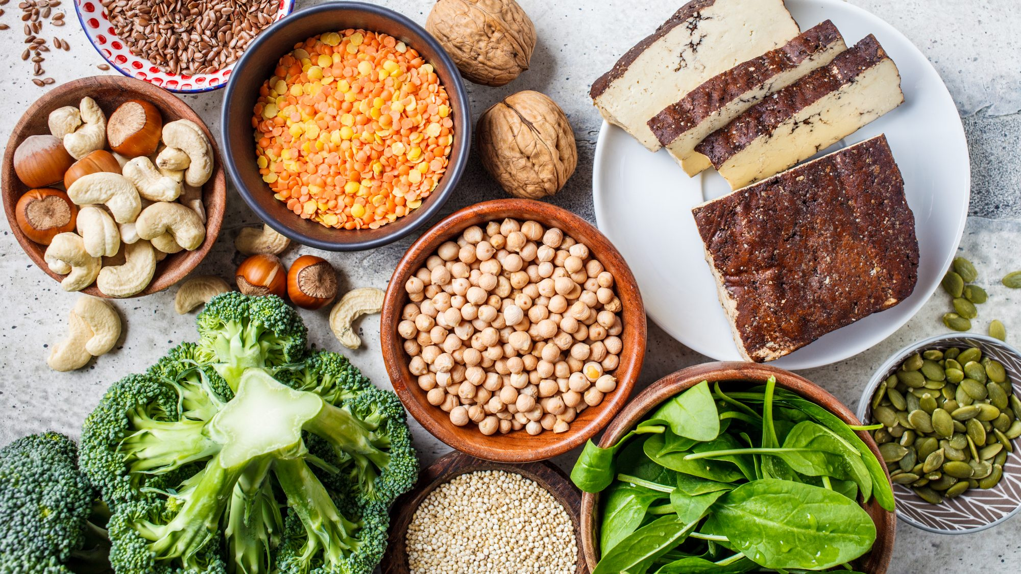 different sources of Vegan protein: lentils, beans, seeds, nuts, and more in bowls on a table