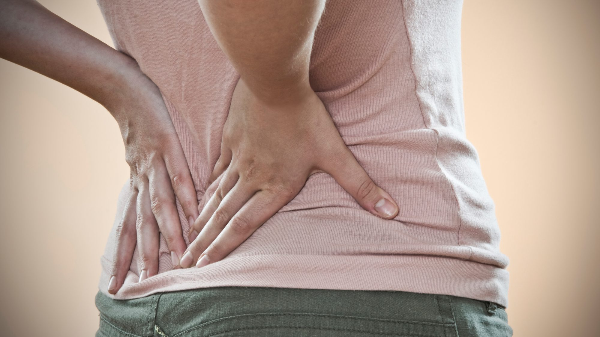 Lower back pain image: woman holding her lower back in pain