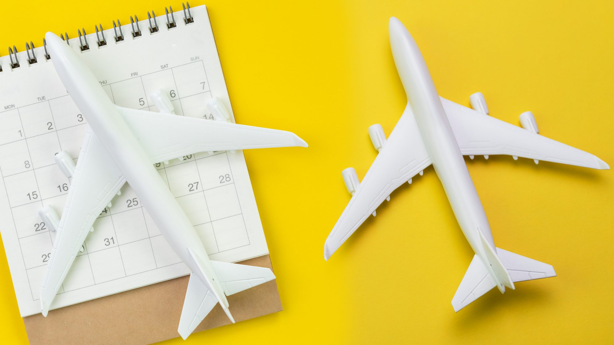 Best time to buy airline tickets - best time, time of year, and day to buy flights: plastic airplanes on calendar