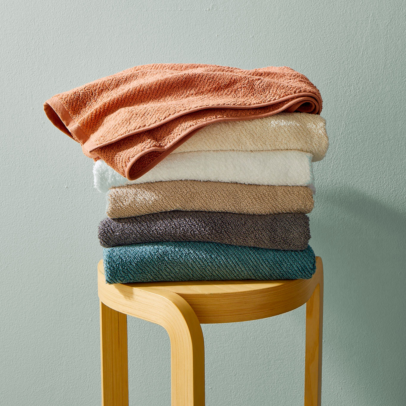 How to pick the best bath towels: stack of towels on stool