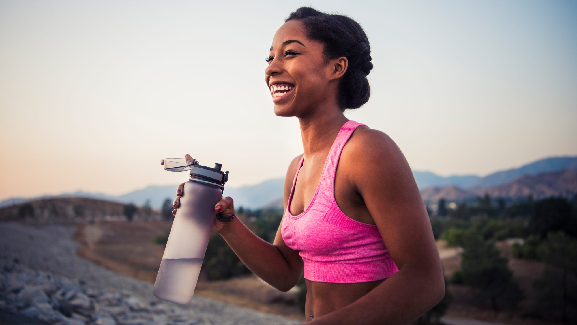 healthy-lifestyle-swaps: woman exercising and drinking water