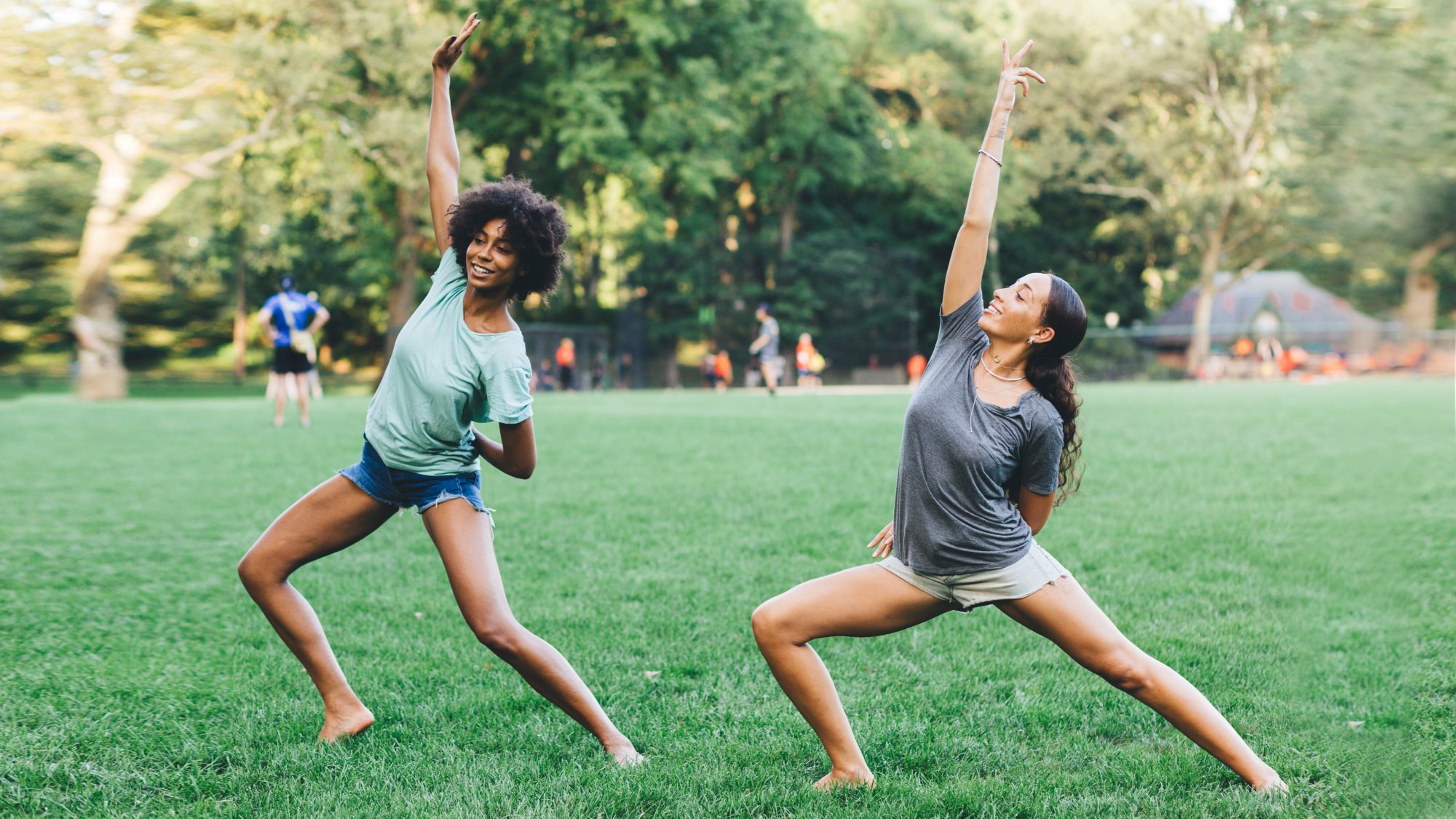 Two women doing yoga outside in a park