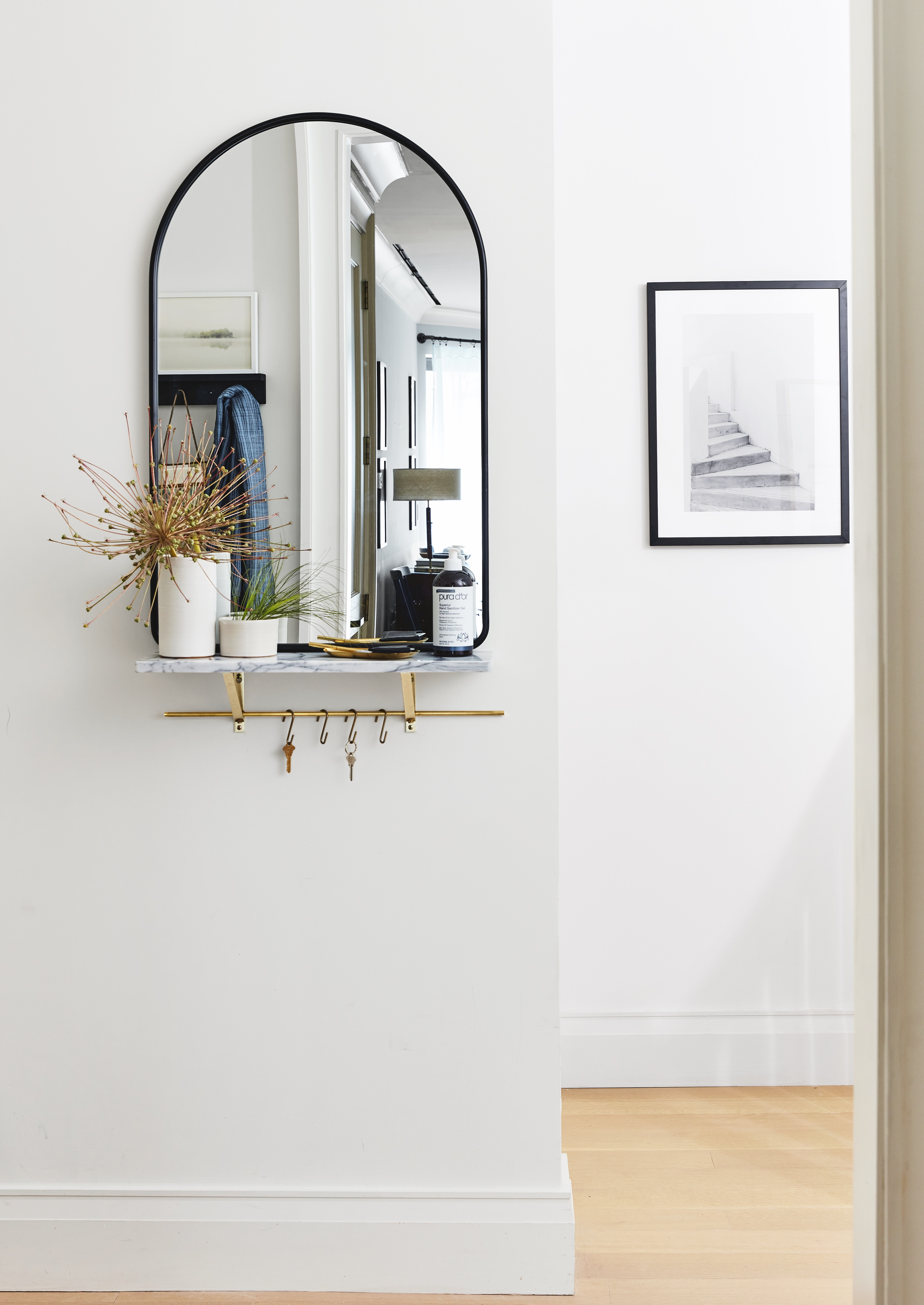 Arched wall mirror and marble shelf with brass brackets
