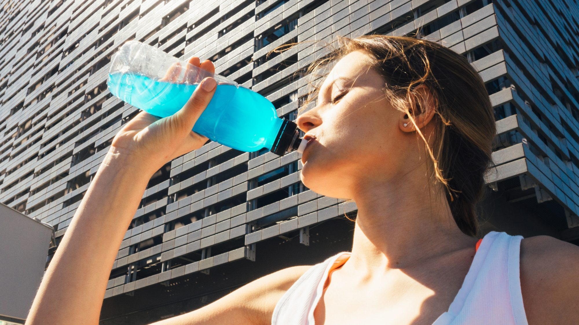 What-are-electrolytes: woman drinking a sports drink while exercising