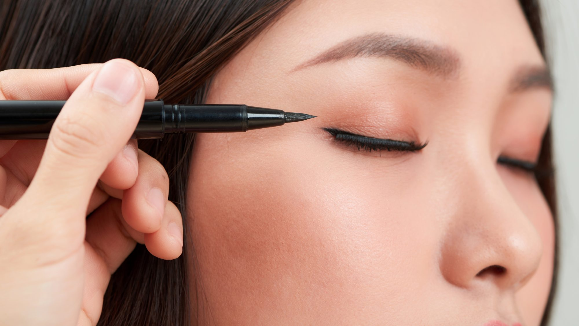 best-eyeliner: woman applying long-lasting liquid eyeliner