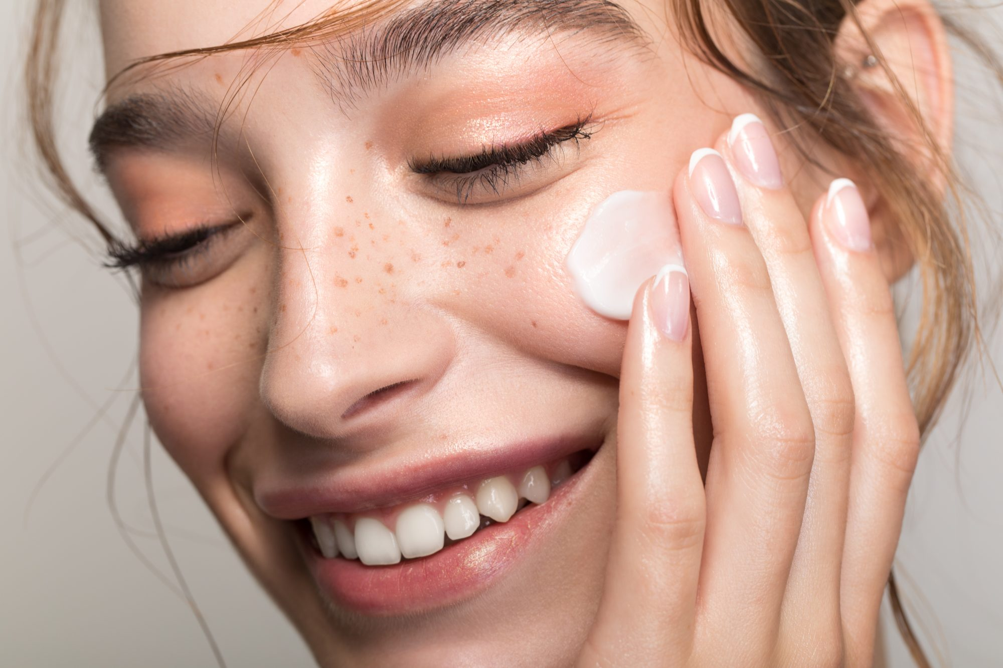 best-products-for-oily-skin: woman applying product to face