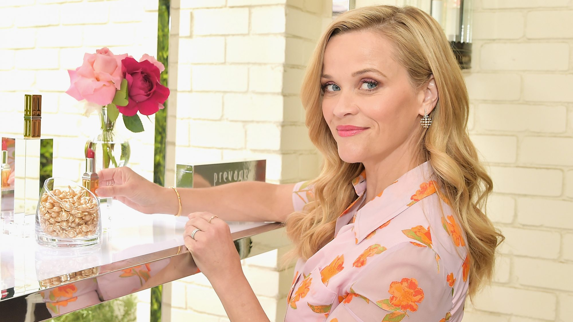 Reese Witherspoon organizes a shelf of beauty products