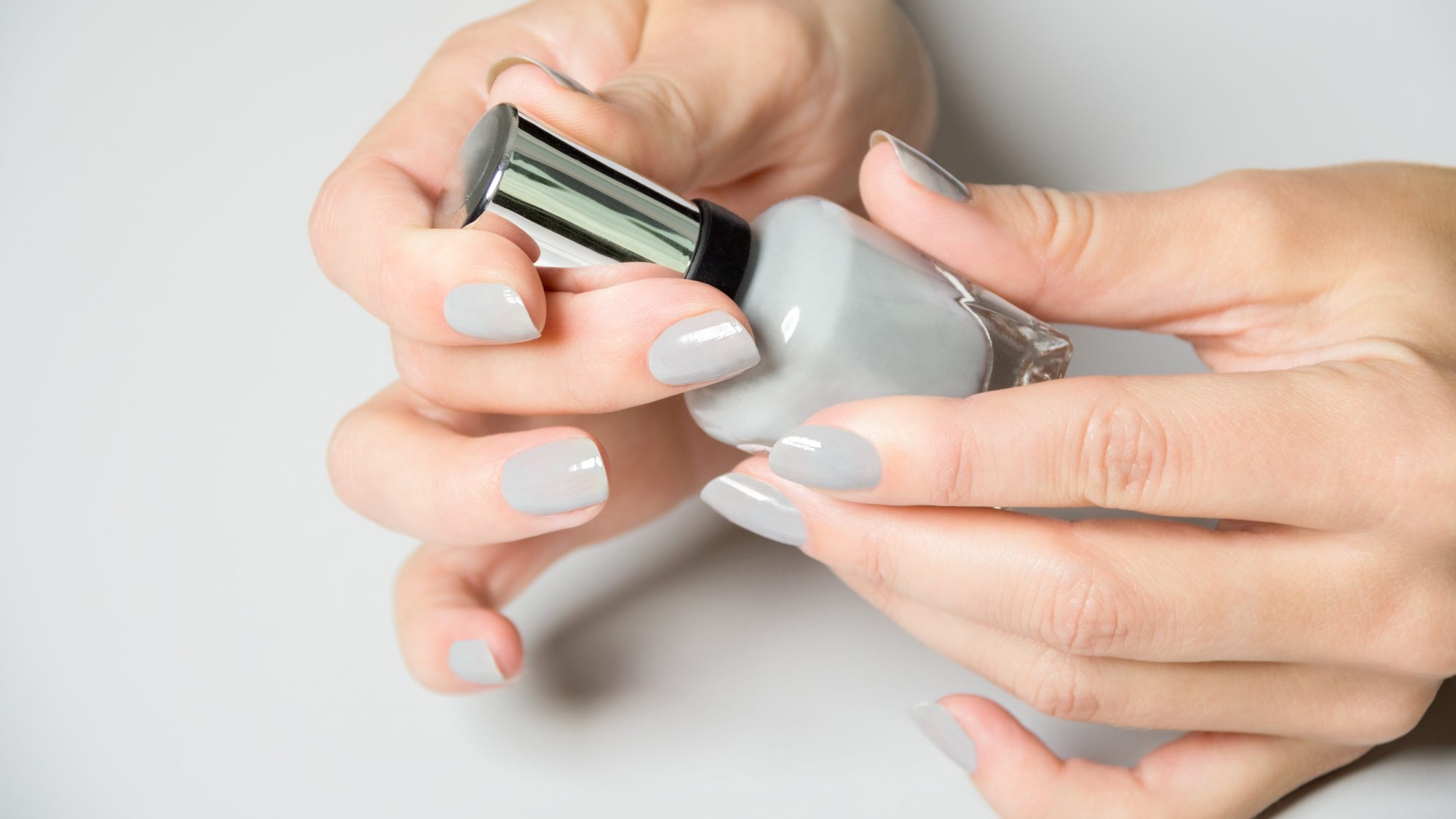 how-to-make-nail-polish-last-longer: woman holding bottle of gray nail polish