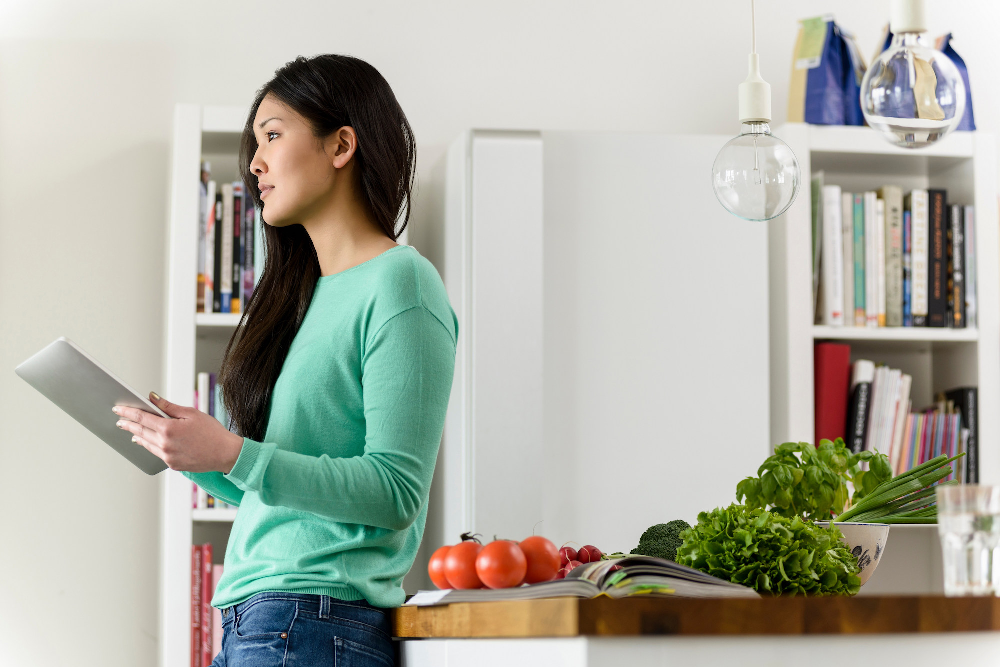 Woman Cooking in Kitchen with Cookbooks