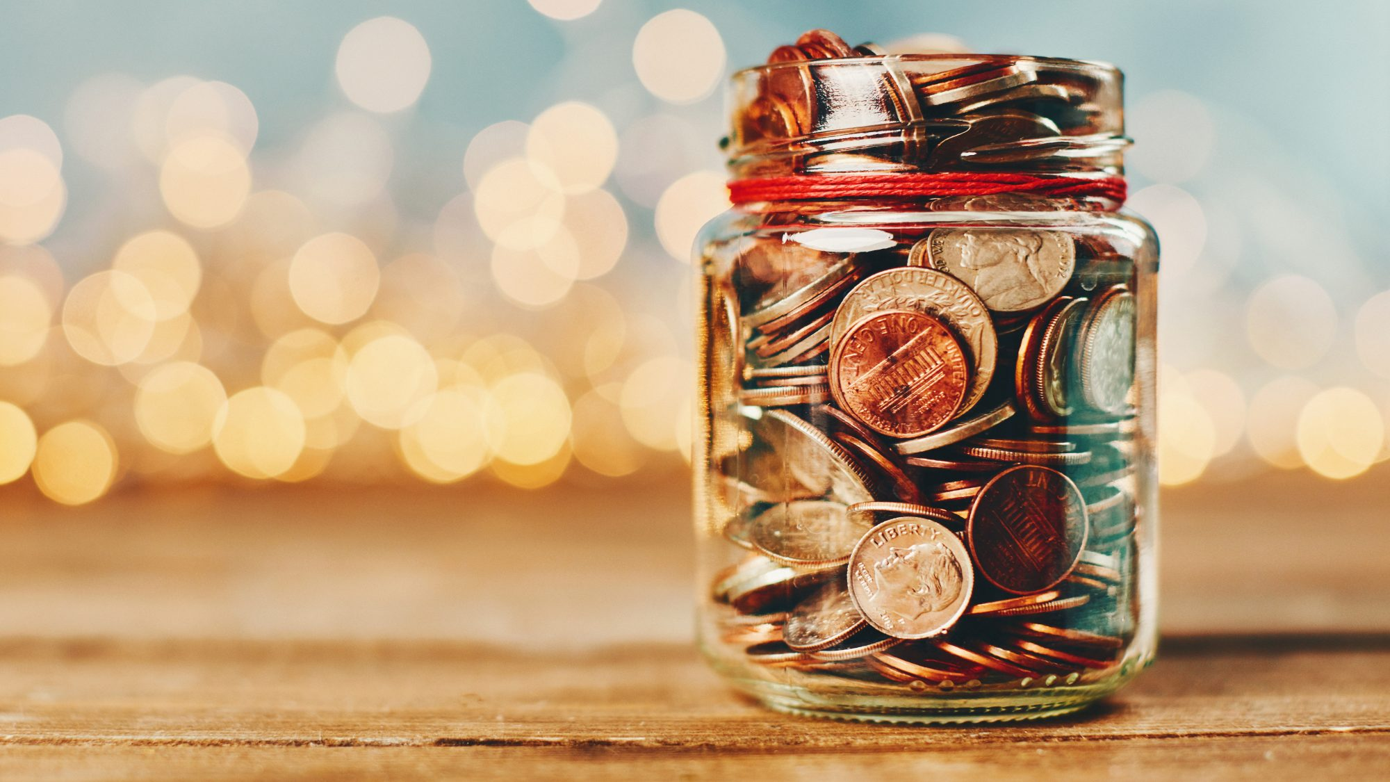 Holiday savings - how to save money during the holidays: coins in a jar