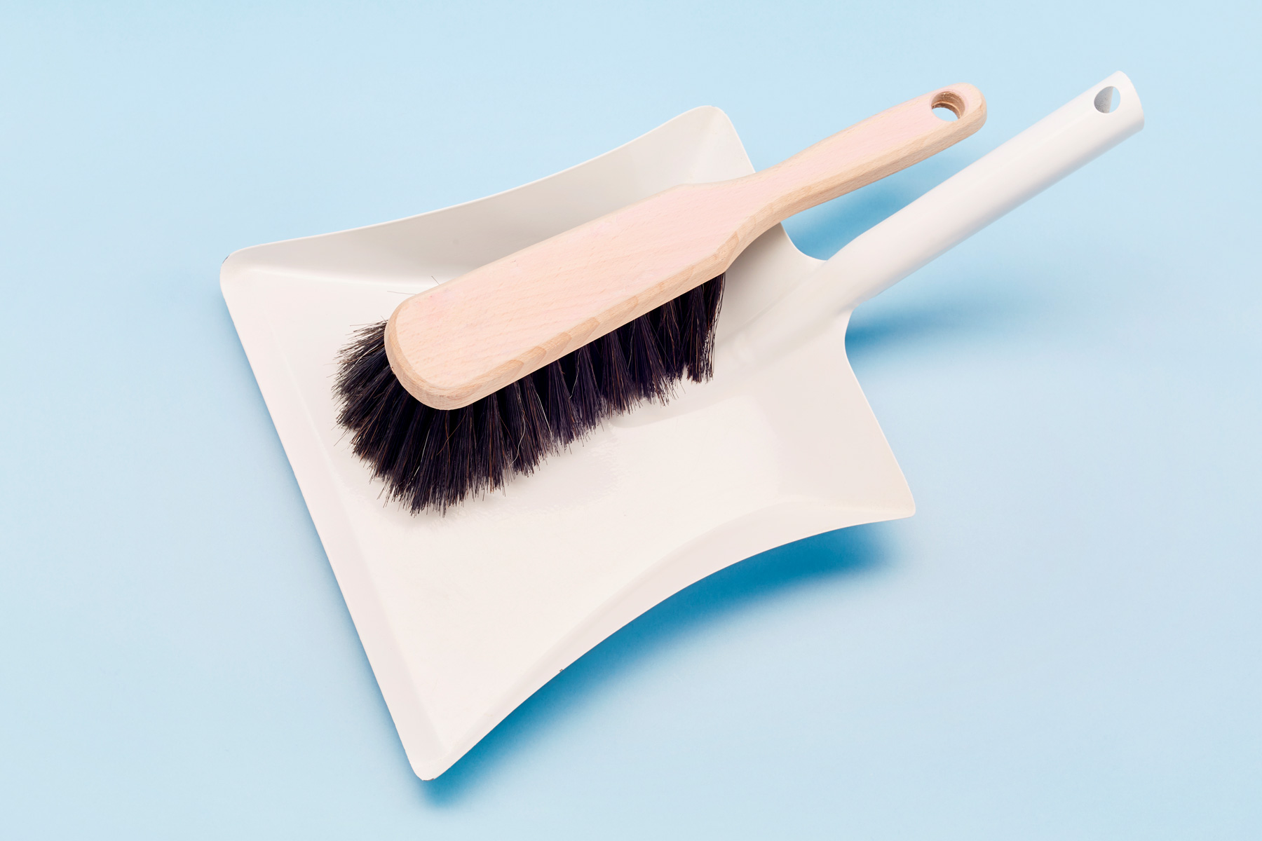 White dust pan and broom on a light blue background