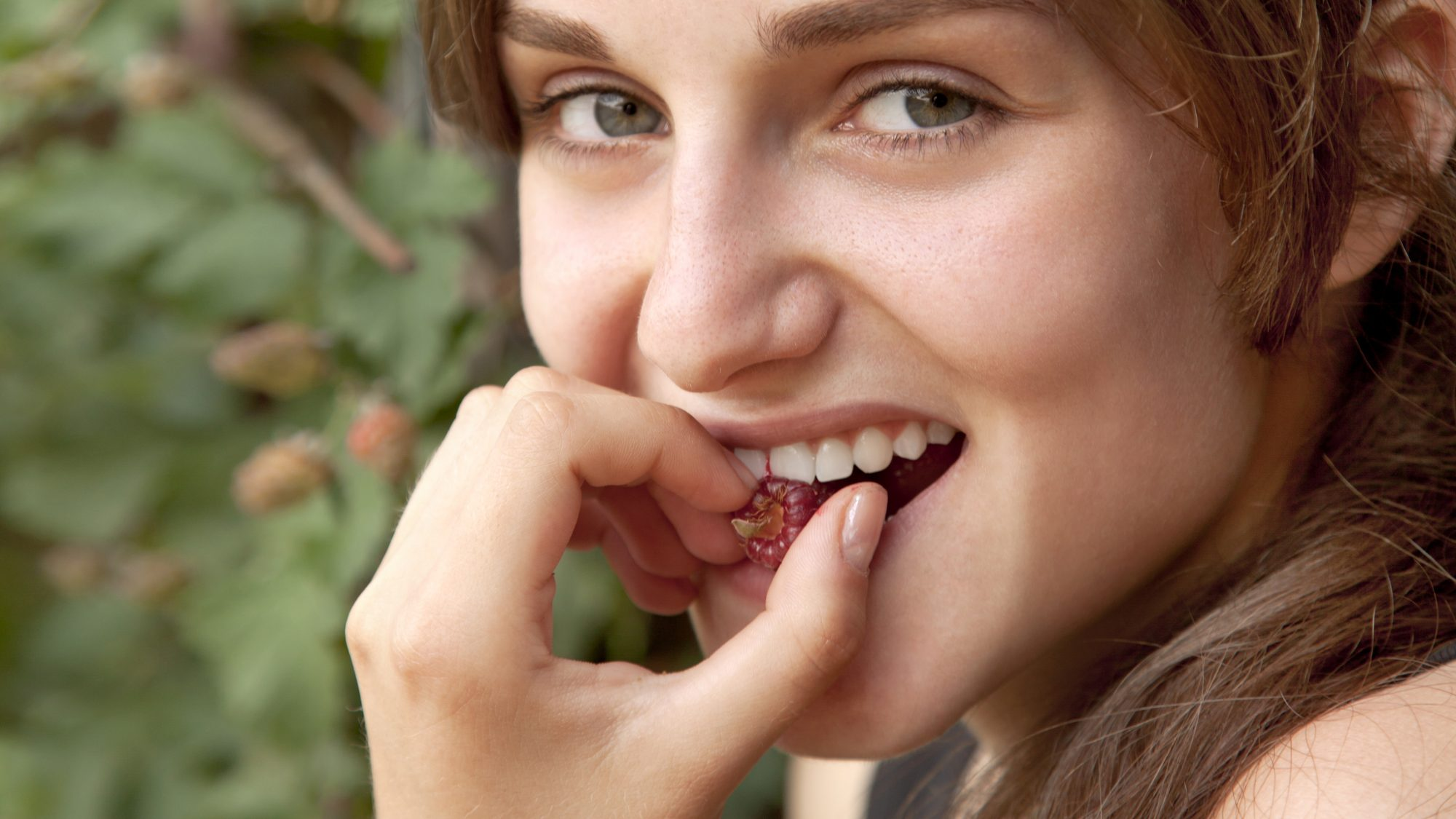sensitive-teeth-causes-and-fixes: woman smiling and biting a raspberry