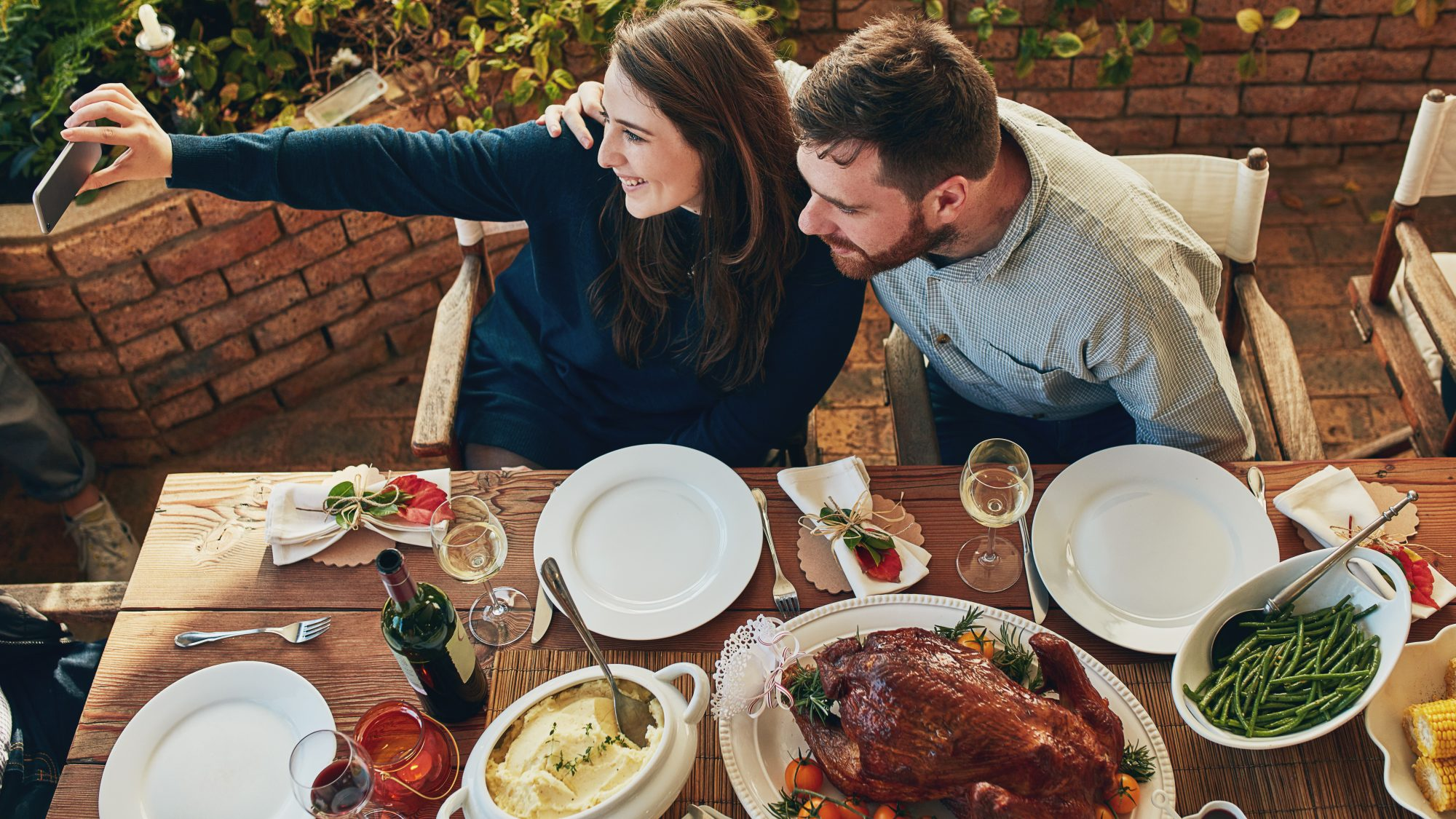 How-to-host-digital-friendsgiving: couple at a table set for Thanksgiving on a video call