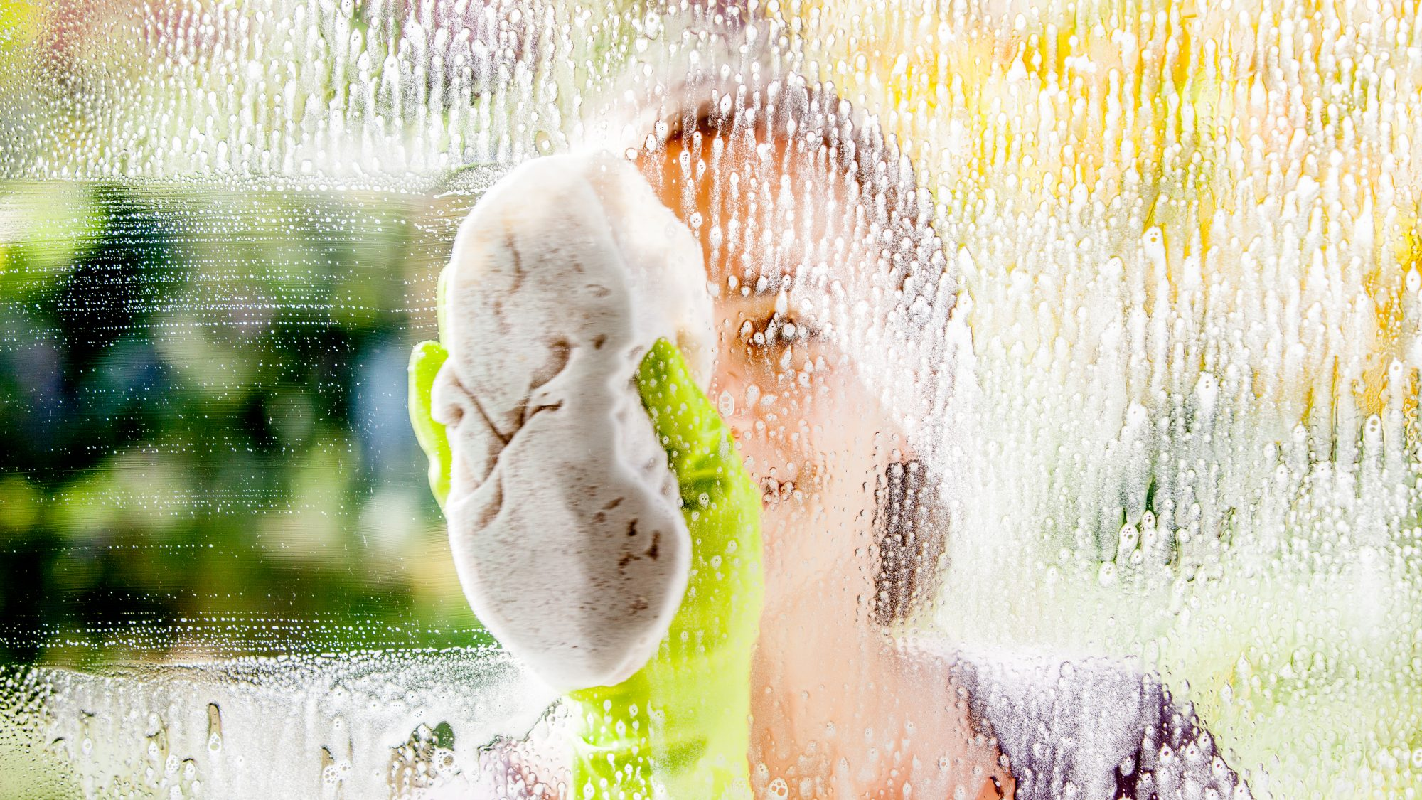 What to Clean Before Winter, woman washing window