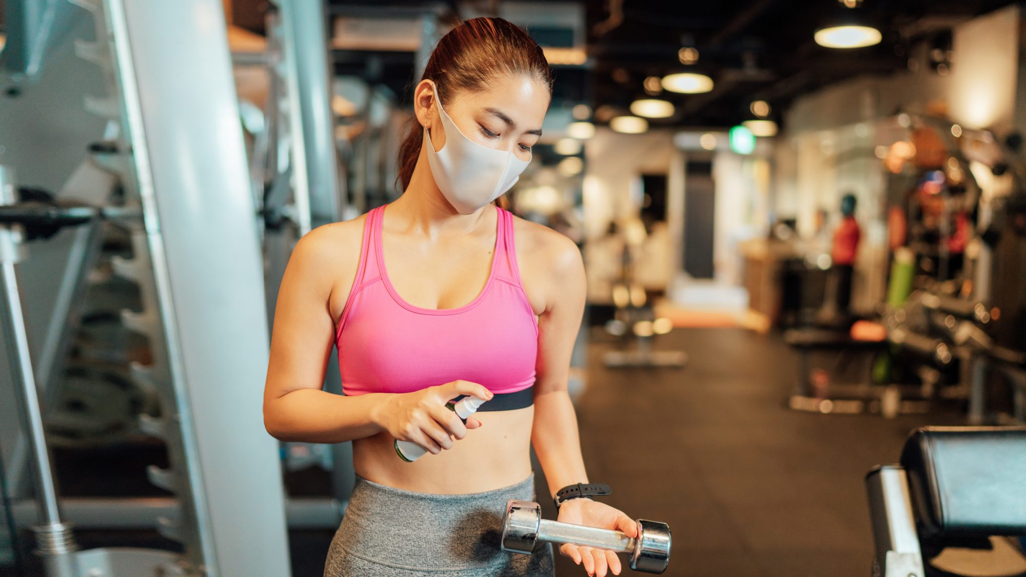 gym-safety-covid: woman at gym with mask and sanitizing equipment
