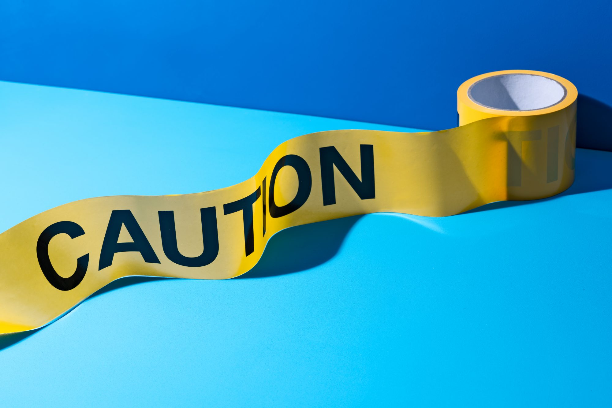 How to Handle Adult Bullies: A Roll of Caution Tape on Blue Colored Background