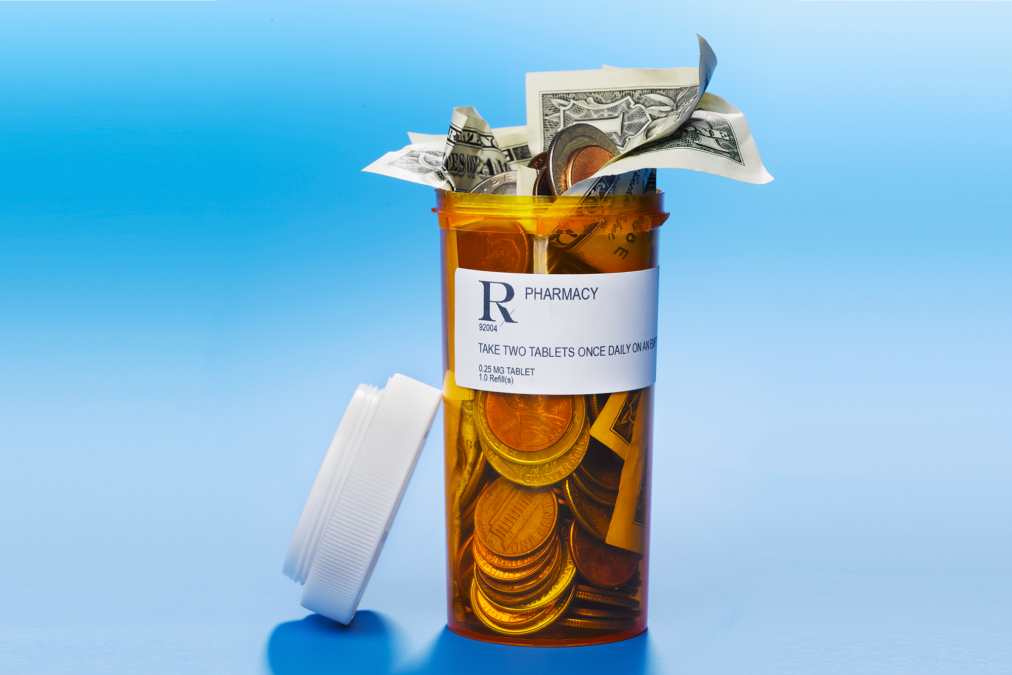 prescription pill bottle with coins and dollar bills.