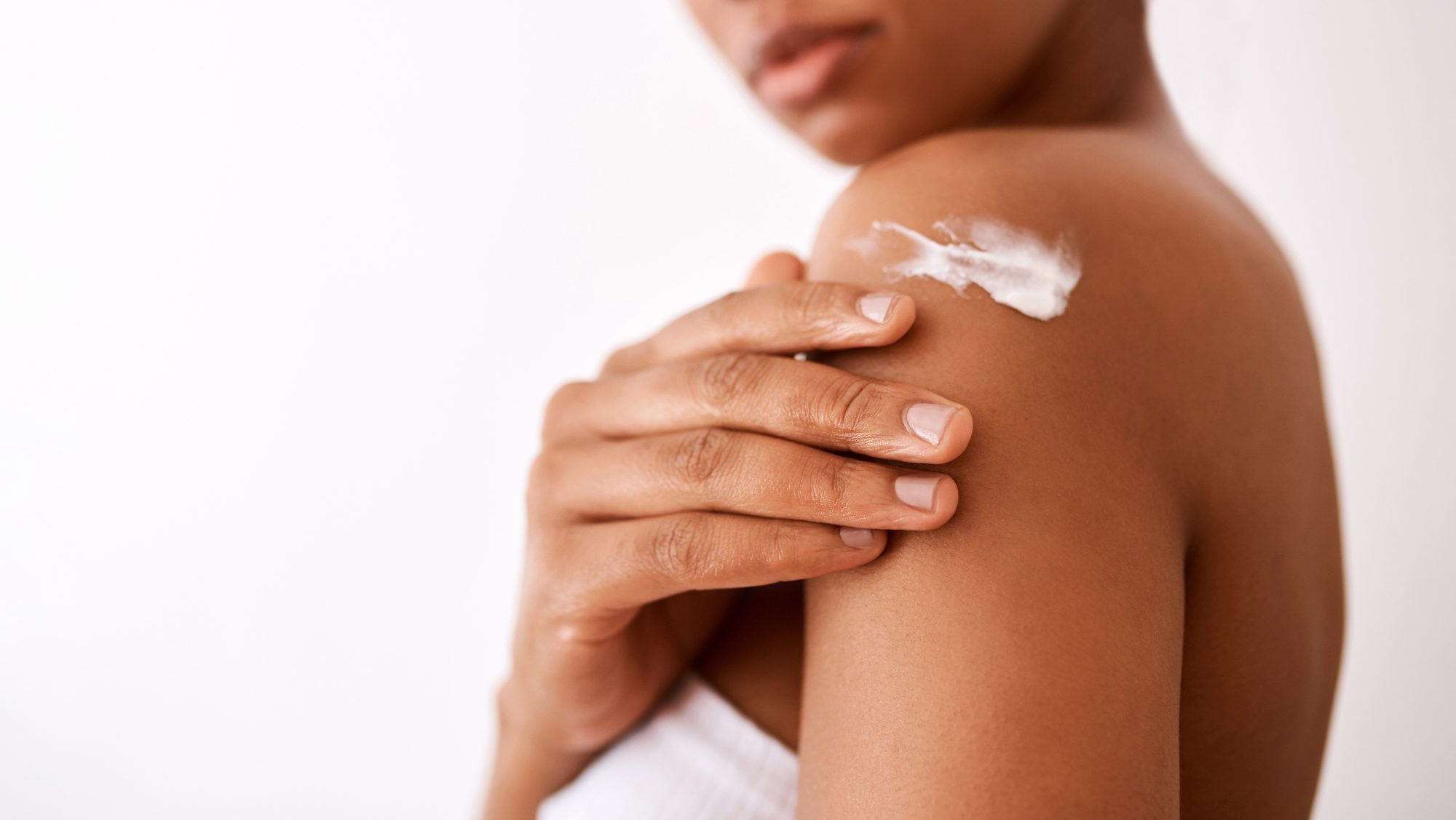 dry-skin-facts: woman applying lotion to skin