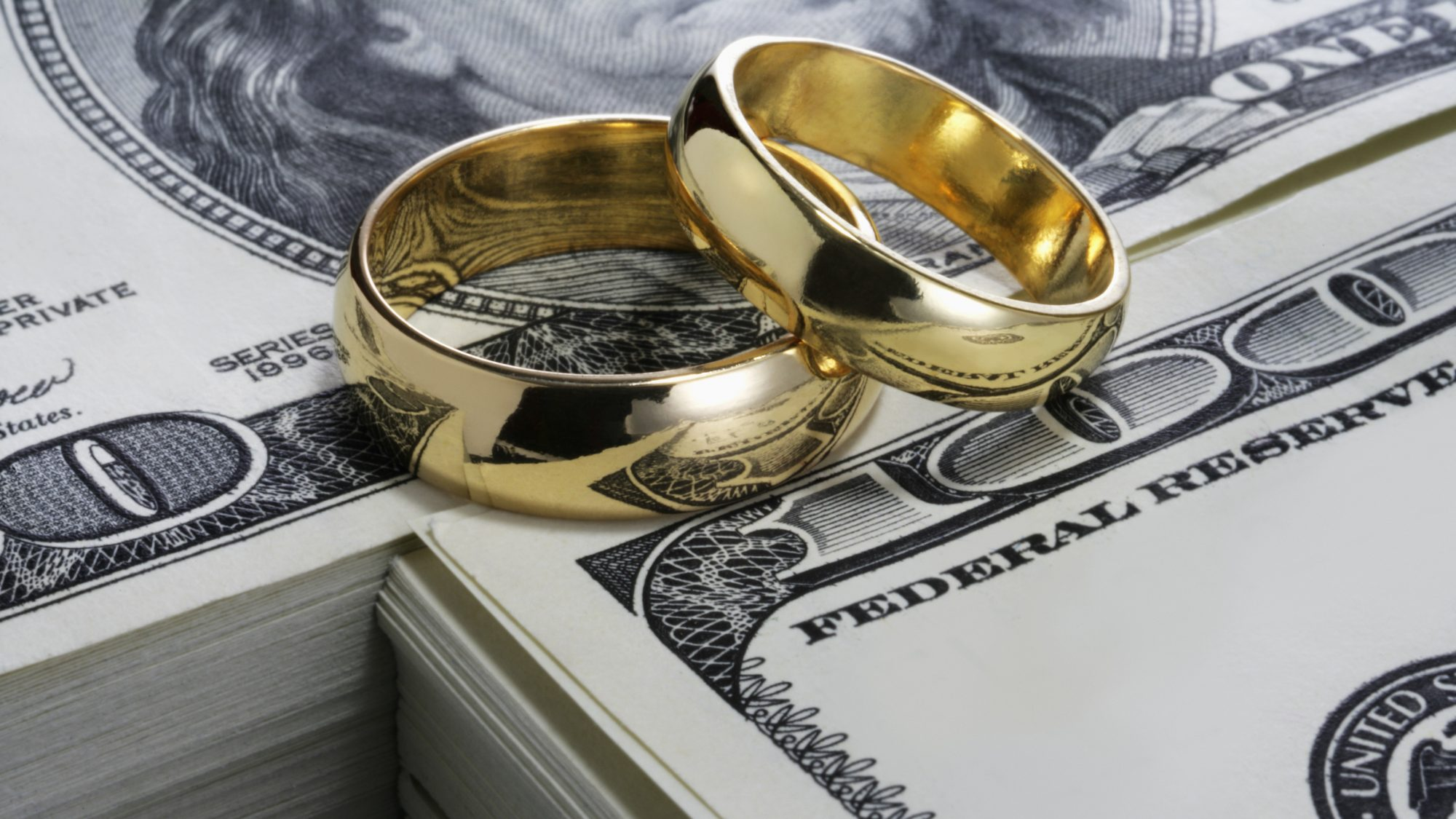 10 Important Things Every Couple Should Do Before Getting Married: gold wedding rings stacked on top of money