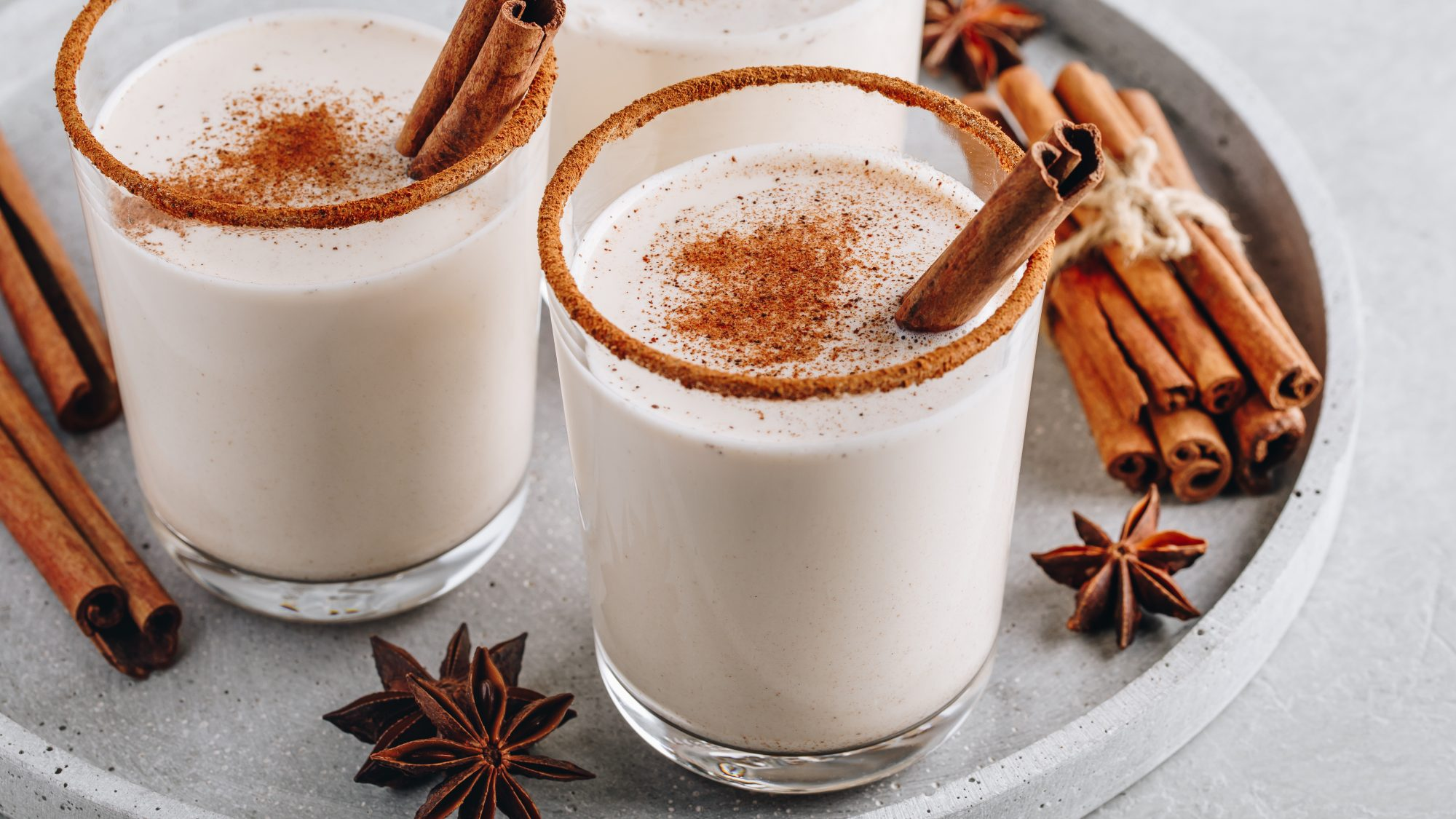 sugary-holiday-foods: Homemade vanilla Christmas drink Eggnog in glass with grated nutmeg and cinnamon sticks