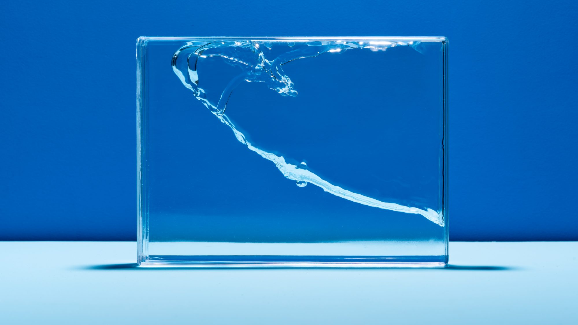 Small Things You Can Do to Save More Water: Water Splash in Glass Box Against Blue Colored Background
