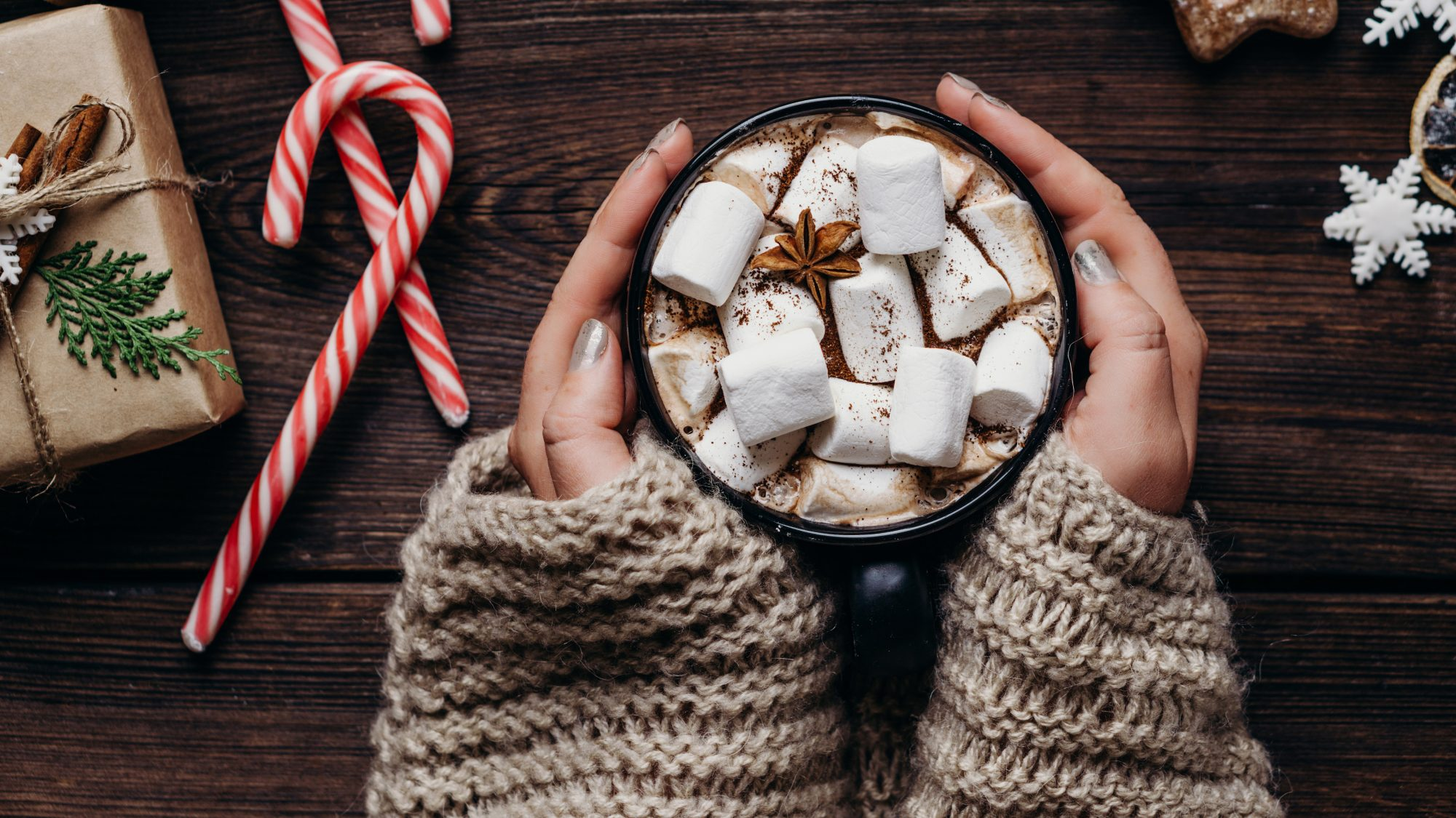 warm-drinks: hands wrapped around a mug of hot cocoa with marshmallows