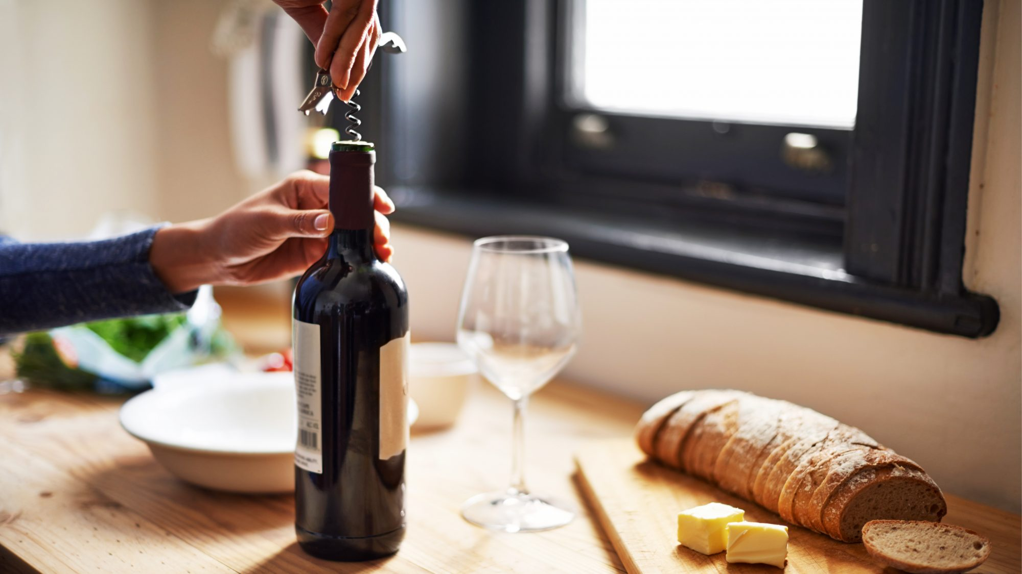 how-to-store-leftover-wine: woman opening bottle of wine