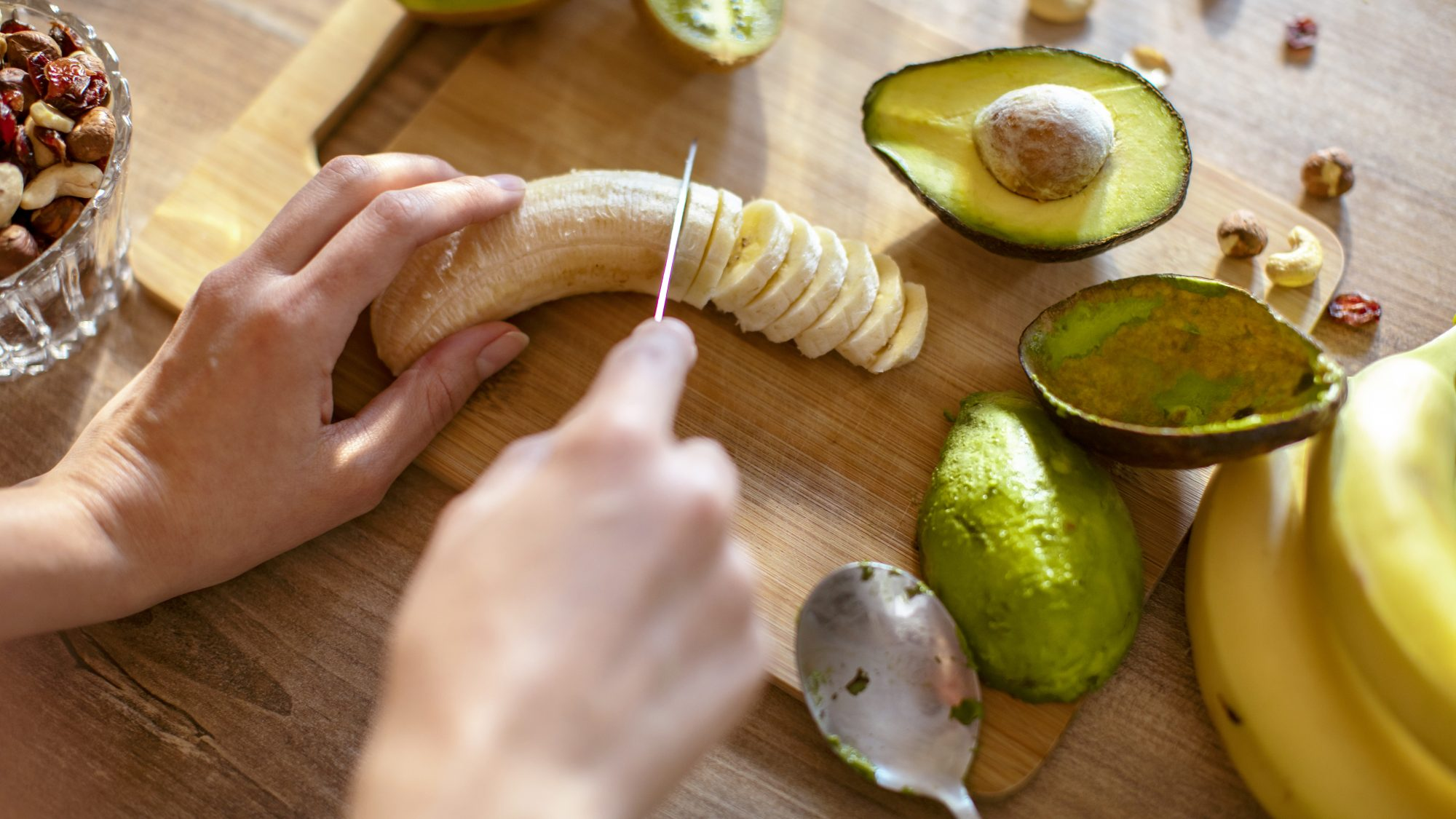 Young woman making a healthy smoothie: slicing banana meal prep