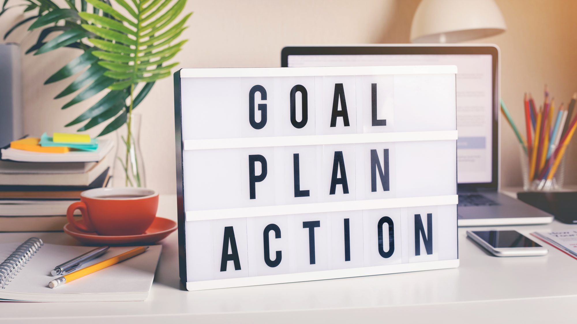 How to Accomplish Goals: Goal Plan Action letter board on a desk