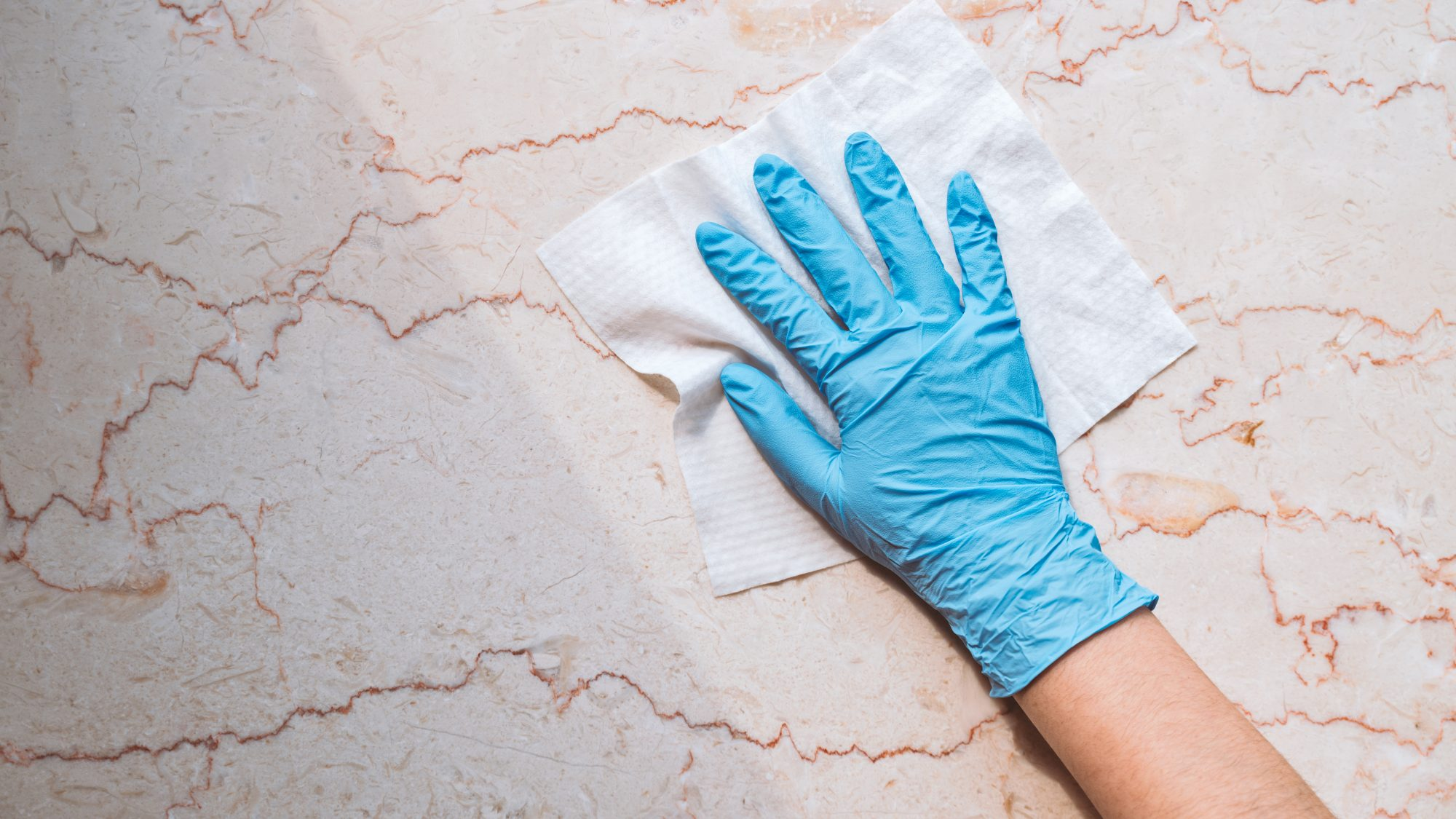 disinfectant-myths: woman wearing rubber gloves, cleaning counter