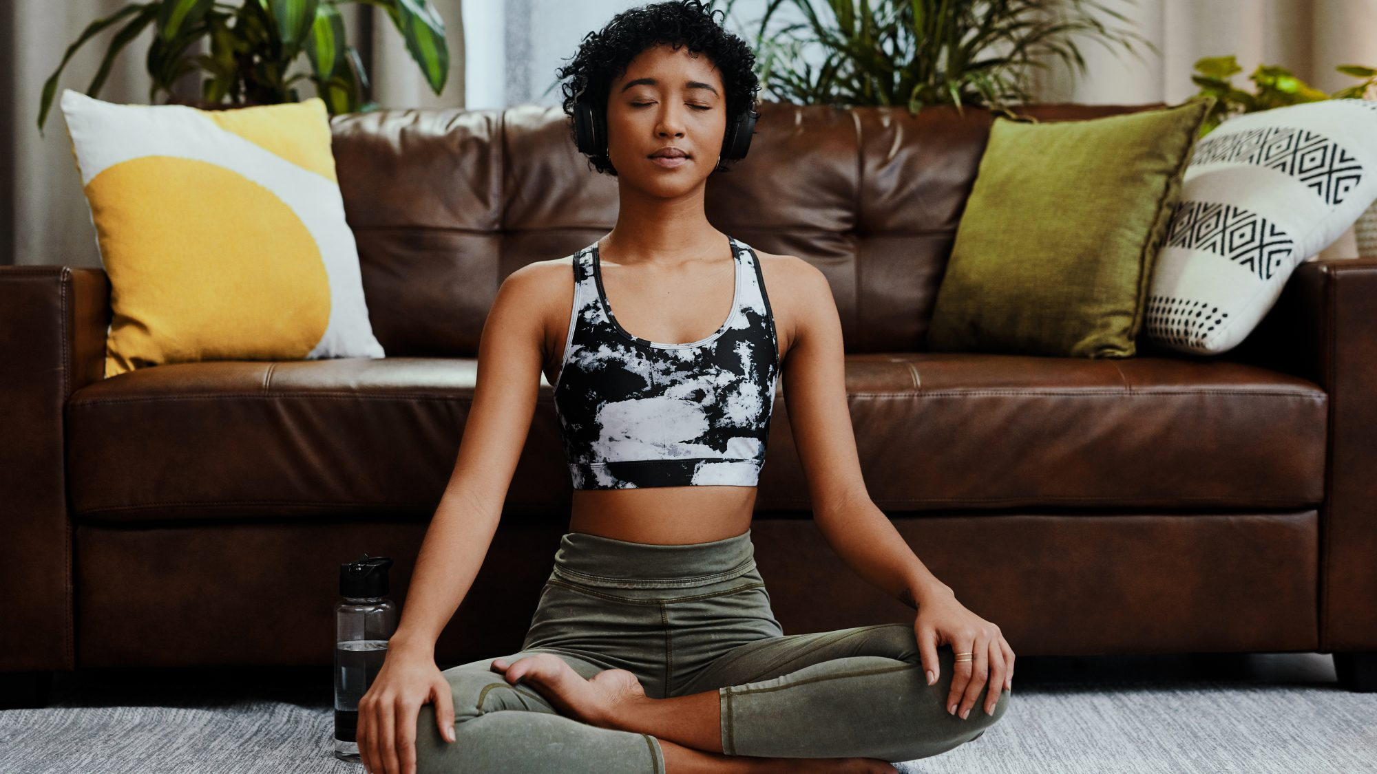23 Small Self-Care Challenges to Try in 2021:Shot of a young woman listening to music while meditating at home