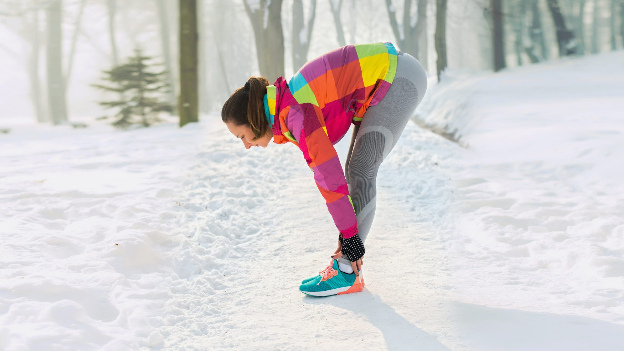 Cold Weather Exercise Risks and Tips: Woman stretching outside in the snow